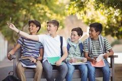 Estudiantes felices que se sientan en banco y que toman el selfie en el teléfono móvil Fotografía de archivo