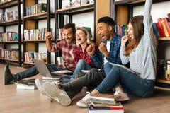 Estudiantes felices que se sientan en biblioteca en piso usando el ordenador portátil Fotos de archivo