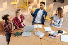 Estudiantes felices que se sientan en la biblioteca que habla con uno a Imagenes de archivo