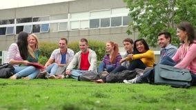 Estudiantes felices que se sientan en la hierba junto que habla metrajes