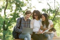 Estudiantes felices que se sientan y que estudian al aire libre mientras que usa el ordenador portátil Fotografía de archivo
