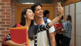 Estudiantes felices que toman el selfie en vestuario metrajes
