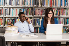 Estudiantes felices que trabajan con el ordenador portátil en biblioteca Fotografía de archivo