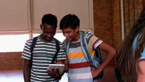 Estudiantes felices que usan el teléfono móvil y la tableta digital en campus metrajes