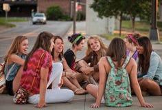 Estudiantes femeninos que se sientan en la tierra Fotografía de archivo libre de regalías