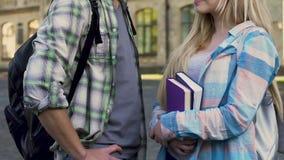 Estudiantes femeninos y masculinos que hablan después de las clases, comienzo de la relación, afecto metrajes