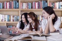 Estudiantes hermosos que discuten con el ordenador portátil Fotografía de archivo libre de regalías