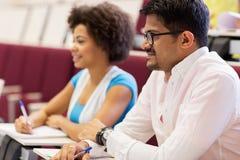 Estudiantes internacionales con los cuadernos en conferencia Fotografía de archivo libre de regalías