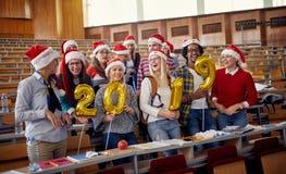 Estudiantes internacionales felices en el sombrero de Papá Noel que celebran día de fiesta foto de archivo