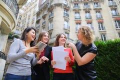 Estudiantes internacionales que pagan con la tarjeta con la tableta en la O.N.U cercana imágenes de archivo libres de regalías