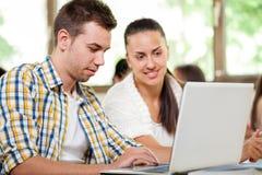 Estudiantes jovenes con el ordenador portátil imagen de archivo libre de regalías