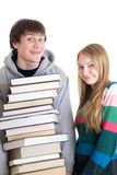 Estudiantes jovenes de los pares con una pila de libros aislados Imagenes de archivo