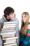 Estudiantes jovenes de los pares con una pila de libros aislados Imágenes de archivo libres de regalías