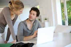 Estudiantes jovenes en casa que estudian en el ordenador portátil Foto de archivo libre de regalías