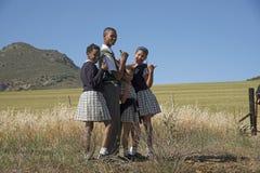 Estudiantes jovenes en el borde de la carretera Suráfrica Fotografía de archivo