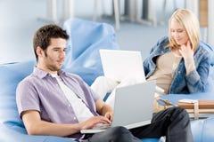 Estudiantes jovenes en la High School secundaria que trabaja en la computadora portátil Imágenes de archivo libres de regalías