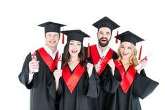 Estudiantes jovenes en los casquillos académicos que sostienen los diplomas y que sonríen en la cámara Fotografía de archivo