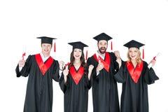 Estudiantes jovenes en los casquillos académicos que sostienen los diplomas y que sonríen en la cámara Imagen de archivo libre de regalías