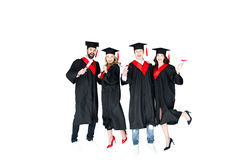 Estudiantes jovenes felices en los casquillos de la graduación con el salto de los diplomas aislados Imagen de archivo libre de regalías