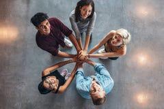Estudiantes jovenes felices que muestran la unidad Fotografía de archivo
