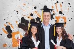 Estudiantes jovenes felices que sostienen los diplomas contra fondo salpicado gris, amarillo y negro Fotografía de archivo