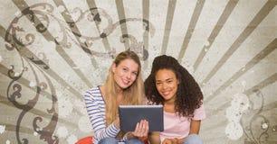 Estudiantes jovenes felices que sostienen una tableta contra fondo salpicado marrón y blanco Imagen de archivo libre de regalías