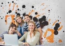 Estudiantes jovenes felices que usan un ordenador contra fondo salpicado gris, amarillo y negro Imágenes de archivo libres de regalías