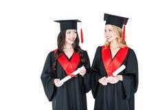 Estudiantes jovenes hermosos en los casquillos académicos que sostienen los diplomas y que se sonríen Foto de archivo