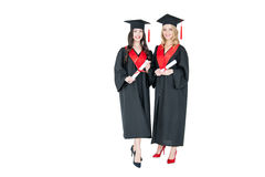 Estudiantes jovenes hermosos en los casquillos académicos que sostienen los diplomas y que sonríen en la cámara Imagenes de archivo