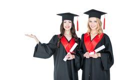 Estudiantes jovenes hermosos en los casquillos académicos que sostienen los diplomas y que sonríen en la cámara Fotos de archivo