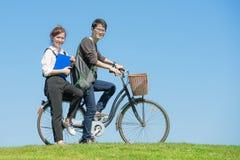 Estudiantes jovenes que completan un ciclo en prado verde de la primavera en universidad Fotografía de archivo