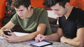 Estudiantes jovenes que estudian con los artilugios Fotografía de archivo libre de regalías