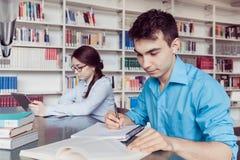 Estudiantes jovenes que estudian en la biblioteca Imagen de archivo libre de regalías