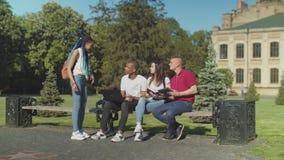 Estudiantes jovenes que estudian la sentada en banco de parque almacen de metraje de vídeo