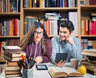 Estudiantes jovenes que leen un ebook Foto de archivo