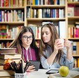 Estudiantes jovenes que leen un ebook Imagen de archivo libre de regalías