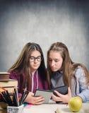 Estudiantes jovenes que leen un ebook Imagenes de archivo