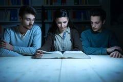 Estudiantes jovenes que leen un libro tarde en la noche Imagen de archivo