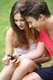 Estudiantes jovenes que leen un mensaje de texto Fotografía de archivo