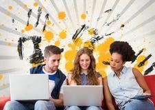 Estudiantes jovenes que miran un ordenador contra fondo salpicado gris, amarillo y negro Fotografía de archivo