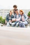 Estudiantes jovenes que se fotografían a través de la tableta digital en el campus Fotos de archivo