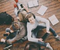 Estudiantes jovenes que se sientan en el piso y estudiar Fotografía de archivo libre de regalías