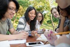 Estudiantes jovenes que se sientan y que estudian al aire libre mientras que habla Imagen de archivo