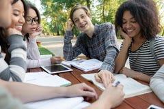 Estudiantes jovenes que se sientan y que estudian al aire libre mientras que habla Fotos de archivo