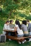 Estudiantes jovenes que se sientan y que estudian al aire libre mientras que habla Imagen de archivo libre de regalías