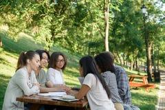 Estudiantes jovenes que se sientan y que estudian al aire libre mientras que habla Foto de archivo