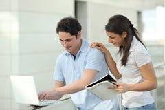 Estudiantes jovenes que sonríen delante de la computadora portátil Fotografía de archivo libre de regalías