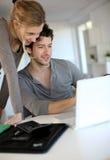 Estudiantes jovenes que trabajan en el ordenador portátil en casa Fotos de archivo