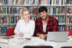 Estudiantes jovenes que usan su ordenador portátil en una biblioteca Imagen de archivo libre de regalías