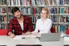 Estudiantes jovenes que usan su ordenador portátil en una biblioteca Fotos de archivo